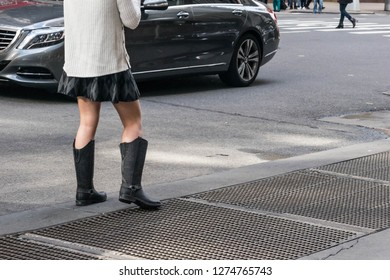 Woman wearing boots and a miniskirt. The model has a foot on a subway grating.