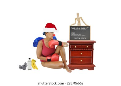 Woman wearing boxing gloves clown nose sitting on floor next to night stand with bananas weights bottled water looking right isolated on white background