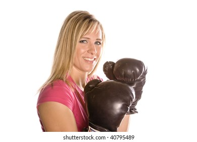 A woman wearing boxing gloves, getting ready to box.