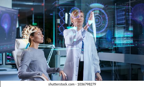 Woman Wearing Brainwave Scanning Headset Sits in a Chair while Scientist Using Futuristic Holografic Interface. In the Modern Brain Study Laboratory Monitors Show EEG Reading and Brain Model.