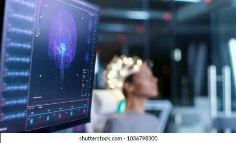Woman Wearing Brainwave Scanning Headset Sits in a Chair In the Modern Brain Study Laboratory/ Neurological Research Center. Monitors Show EEG Reading and Brain Model.