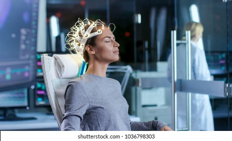 Woman Wearing Brainwave Scanning Headset Sits in a Chair while Scientist Supervises. In the Modern Brain Study Laboratory Monitors Show EEG Reading and Brain Model.