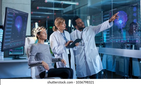 Woman Wearing Brainwave Scanning Headset Sits in a Chair while Two Scientists Supervise and Look at Data. In the Modern Brain Study Laboratory Monitors Show EEG Reading and Brain Model.