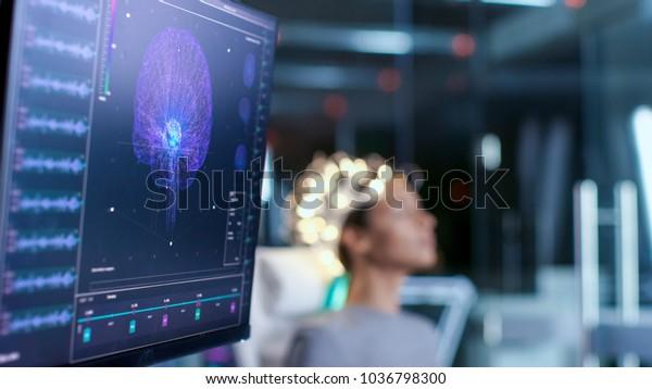 Frauen tragen Hirnwellenscanning Headset Sits in einem Stuhl im modernen Gehirnstudilabor/ neurologischen Forschungszentrum. Monitore zeigen EEG Reading und Gehirnmodell.