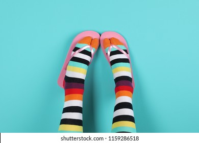 Woman wearing bright socks with flip-flops on color background