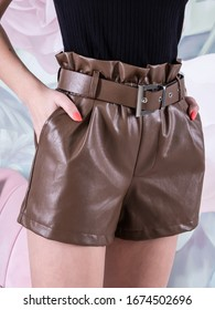 Woman wearing brown leather shorts