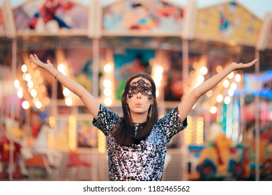 Woman Wearing carnival Mask at Funfair Amusement Park. Mysterious masked playing masquerade  girl at festival