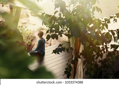 Woman wearing casual close sitting in lotus pose, relaxing and meditate outdoor in ocean garden