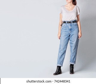 Woman wearing casual outfit with white t-shirt, blue vintage high-waisted with black ankle boots and black belt isolated on grey background. Copy space