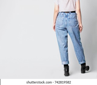 Woman wearing casual outfit with white t-shirt, blue vintage high-waisted mom jeans with black ankle boots and black belt isolated on grey background. Copy space. Fashion details