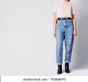 Woman wearing casual outfit with white shirt, blue vintage high-waisted mom jeans with black ankle boots and black belt isolated on grey background. Copy space