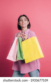 Woman wearing casual sweater on background happy enjoying shopping holding colorful bags