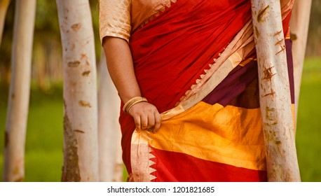 Woman wearing colourful saree standing around a place unique photo