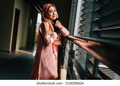 Woman wearing conservative Hijab fashion while walking in a modern urban city. The female wearing religious muslim outfit represents individualism  feminism and ethnic and racial acceptance.