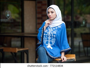 Woman wearing conservative Hijab fashion posing to a camera during portraiture session. The female wearing religious muslim outfit represents individualism, feminism and ethnic and racial acceptance.