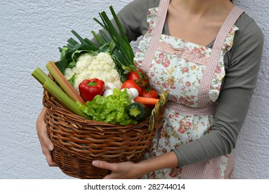 A woman wearing a cooking apron is showing a wicker basket full of fresh vegetables