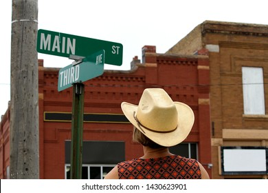 A woman wearing a cowboy hat standing in front of a typical Main Street sign in a rural town in the United States of America.  There are old vintage looking brick buildings visible in the background.