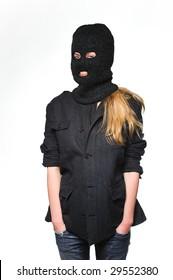 A woman wearing dark clothes and a black ski mask like a terrorist.