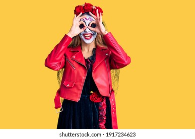 Woman wearing day of the dead costume over background doing ok gesture like binoculars sticking tongue out, eyes looking through fingers. crazy expression.