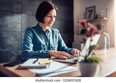 Woman wearing denim shirt using laptop in the office