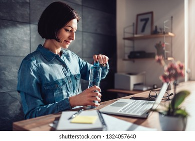 Woman wearing denim shirt working in the office and opening plastic bottle of water