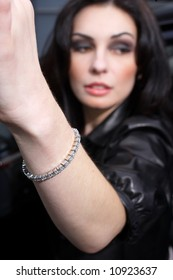A woman wearing a diamond tennis bracelet getting out of her car