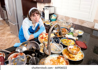 A woman wearing dish washing gloves and an apron contemplates doing the dishes.