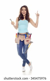 A woman wearing a DIY tool belt full of a variety of useful tools in a workshop. DIY woman.