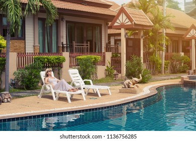Woman wearing dress and hat seating and relaxing near swimming pool in luxury resort. Sunny summer day in Thailand