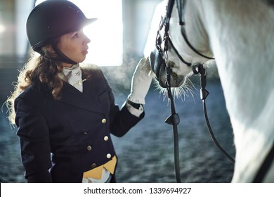 Woman wearing dressage costume fixing harness on a horse