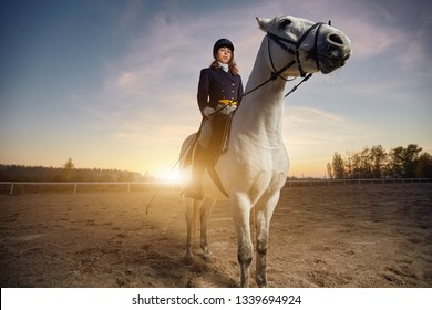 Woman wearing dressage costume riding a horse