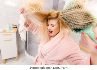 Woman wearing dressing gown trying to brush her long blonde very tangled hair, morning beauty routine. Haircare problem and hairstyling concept.