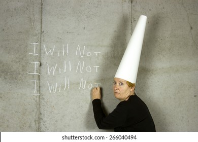 Woman wearing a dunce cap writing I WILL NOT on a concrete wall