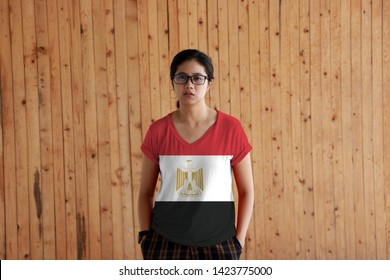 Woman wearing Egypt flag color shirt and standing with two hands in pant pockets on the wooden wall background, red white black color with the Egyptian eagle of Saladin.