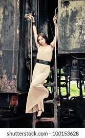 Woman wearing an elegant dress, standing on the steps of the old train