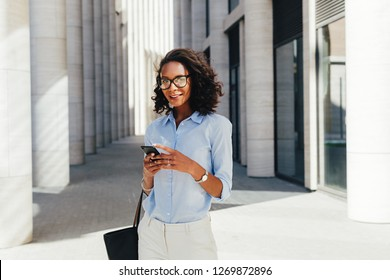 Woman wearing eyeglasses holding a smartphone in hands
