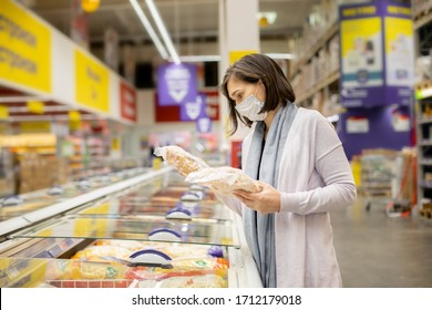 Woman wearing face mask buying in supermarket.Panic shopping during Coronavirus covid-19 pandemic. Budget buying at a supply store. Buying freezer smart purchased household pantry groceries