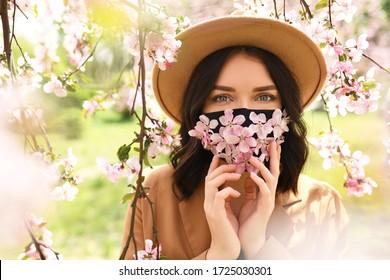 Die Frau trägt eine mit Blumen verzierte Gesichtsmaske. Stilvolle handgefertigte Baumwollmaske. Frühlingsblütengarten