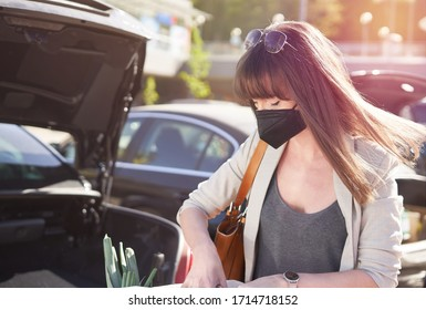 Woman wearing face mask in front supermarket in outdoor parking place, putting grocery bags into car after shopping. Covid-19 virus prevention.