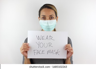 Woman wearing a face mask and holding a sign to wear your face mask