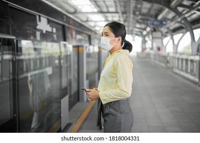 Mujer con máscara facial y parada en el tren aéreo. Protección Coronavirus (COVID-19), Nuevo concepto de viaje normal.