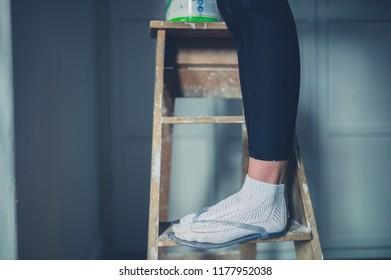 A woman wearing flip flops is standing on a ladder