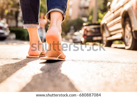 0bb22ef52aeb0 Woman wearing Flip Flops walking down the street on a sunny summer day-  closeup of
