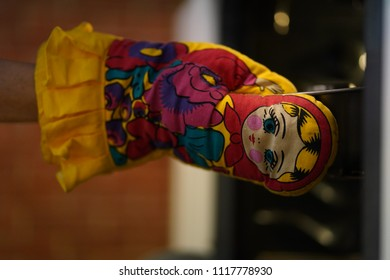Woman wearing fun colorful oven mitt removing cake from oven as she bakes