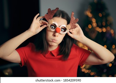 Woman Wearing Funny Christmas Party Glasses. Silly girl in disguise eyeglasses having fun on holidays