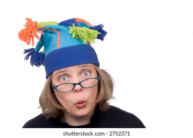 Woman wearing a funny court jester winter hat and making a funny face isolated over white