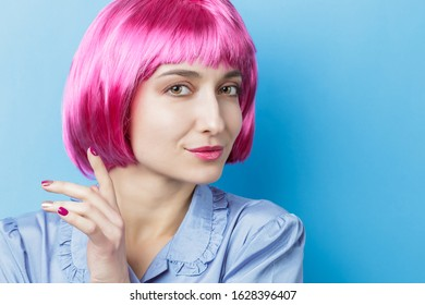 Woman wearing funny pink wig and smiling to the camera over blue background. Short bob and fringe haistyle. Copy space for your text