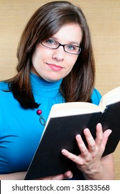 Woman Wearing Glasses Holding And Reading A Book