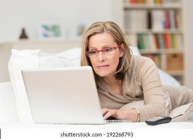 Woman wearing glasses lying on a sofa at home concentrating as she works on a laptop