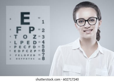 Woman wearing glasses with Snellen test chart on background.